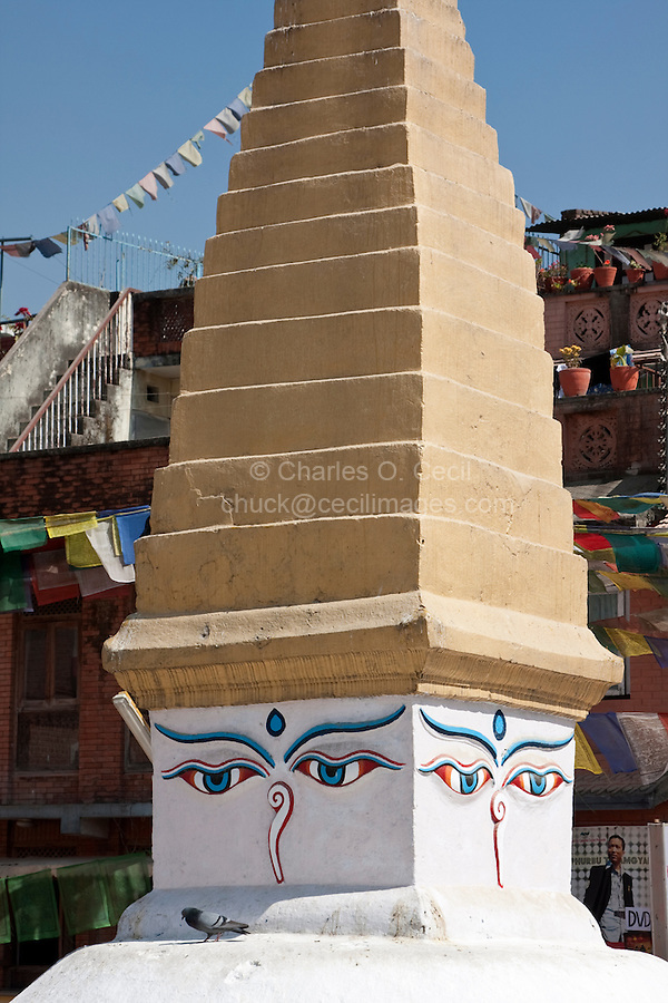 Bodhnath, Nepal.  Eyes of the Buddha Look out from a Small Stupa adjacent to the main Stupa of Bodhnath.  Above the square base, the rising pyramidal levels represent the stages of perfection on the way to nirvana.