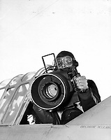 """The Photo squadron personal, planes, and cameras equipment.  Photo students sight thru the view finders of 3 aerial cameras and lenses.  How the F56  20"""" lens camera is hand held for oblique aerial photographs.   Weight 43 Lbs.  Location: NAS Pensacola, Florida."""
