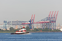 """Tugboat """"Captain D"""" in Newark Bay, with the container cranes of the New York Container Terminal, the Goethals Bridges, and the Arthur Kill Vertical Lift Railroad Bridge in the background."""