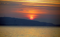 Pictured: The sun rises over Kilvey Hill in Swansea, as seen from West Cross in south Wales, UK. Wednesday 21 June 2017<br />