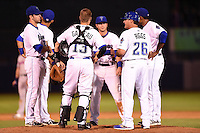 Tulsa Drillers manager Kevin Riggs (26) makes a pitching change as third baseman Jayson Langfels (28), shorstop Cristhian Adames (2), catcher Dustin Garneau (13), second baseman Taylor Featherston (12) and first baseman Harold Riggins (35) look on during a game against the Midland RockHounds on May 31, 2014 at ONEOK Field in Tulsa, Oklahoma.  Tulsa defeated Midland 5-3.  (Mike Janes/Four Seam Images)