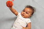7 month old baby boy grasping cloth ball holding it up and looking at it