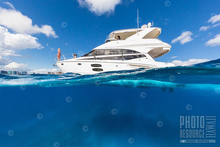 Friends enjoy a beautiful day aboard a white power cruiser in the waters off of Waikiki, Honolulu, O'ahu.