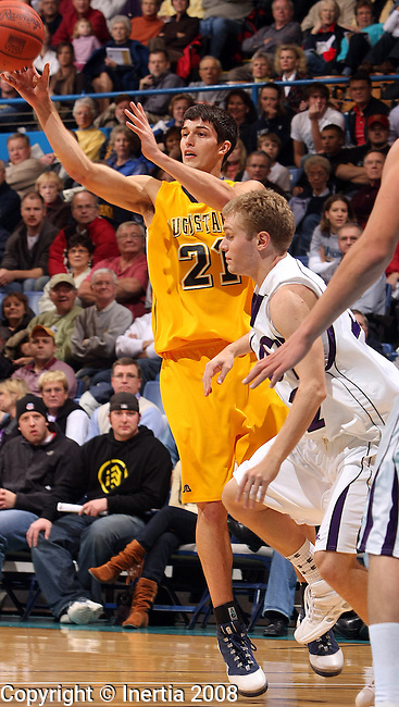 SIOUX FALLS, SD - NOVEMBER 19:  Cody Schilling #21 of Augustana dishes the ball to a teammate as Jack Ridgeway #22 of the University of Sioux Falls defends in the first half of the Prairie Spirit Challenge Wednesday night at the Sioux Falls Arena. (Photo by Dave Eggen/Inertia)