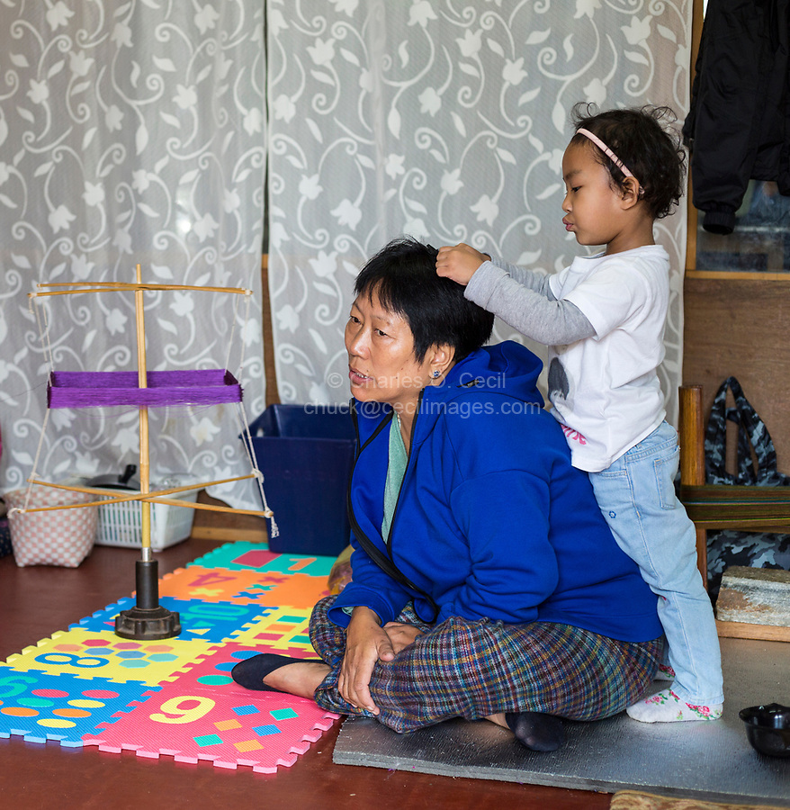 Thimphu, Bhutan.  Little Girl Playing with her Mother's hair.