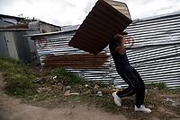 BOGOTA - COLOMBIA, 27-05-2020: Joven habitante del barrio Altos de La Estancia, carga un techo de madera para construir la casa de un perro. Mas de 200 familias terminan el proceso de desalojo en el predio La Estancia al sur de Bogotá quedando sin ninguna ayuda ni un techo donde vivir durante la cuarentena total en el territorio colombiano causada por la pandemia  del Coronavirus, COVID-19. / Young inhabitant of the Altos de La Estancia neighborhood, carries a wooden roof to build a dog's house. More than 200 families are evicted from La Estancia farm at south of Bogota city and they left withoput any help and shelter to live during total quarantine in Colombian territory caused by the Coronavirus pandemic, COVID-19. Photo: VizzorImage / Mariano Vimos / Cont