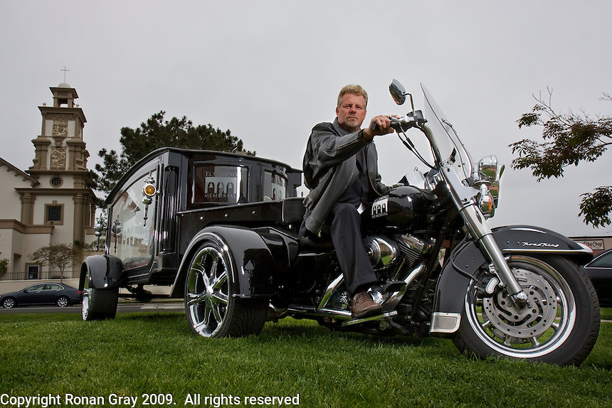"""May 29 2009, Pacific Beach, California, USA.  Douglas G. Trobaugh of Pacific Beach Chapel Funeral Home sits on his Harley Davidson Trike Hearse.  Nicknamed """"The Last Ride"""", the hearse is becoming a popular choice for the funerals of local bike enthusiasts."""