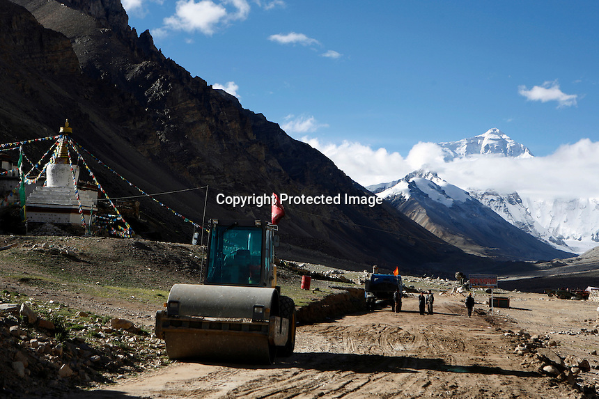 """China started building a controversial 67-mile """"paved highway fenced with undulating guardrails"""" to Mount Qomolangma, known in the west as Mount Everest, to help facilitate next year's Olympic Games torch relay./// A steamroller sits outside Rongbuk Monastery  on the road to Everest Base Camp.<br /> Tibet, China<br /> July, 2007"""