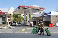 Dakar, Senegal.  Modern Gas Station, Two Street Cleaners Walking By.