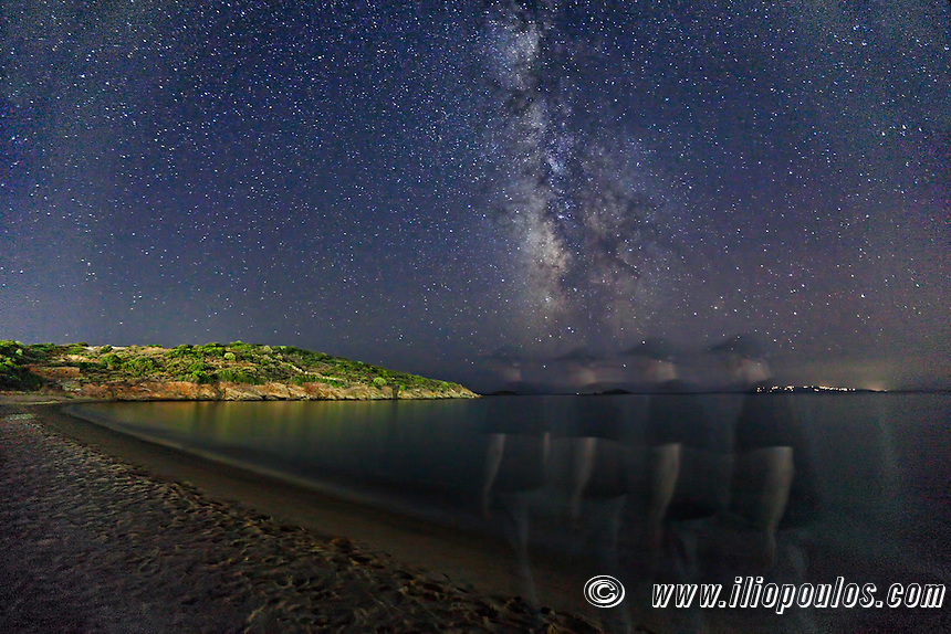 A man walking under the Milky Way on the beach