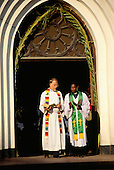 Zanzibar, Tanzania. A black priest and a white priest at the door of their church.