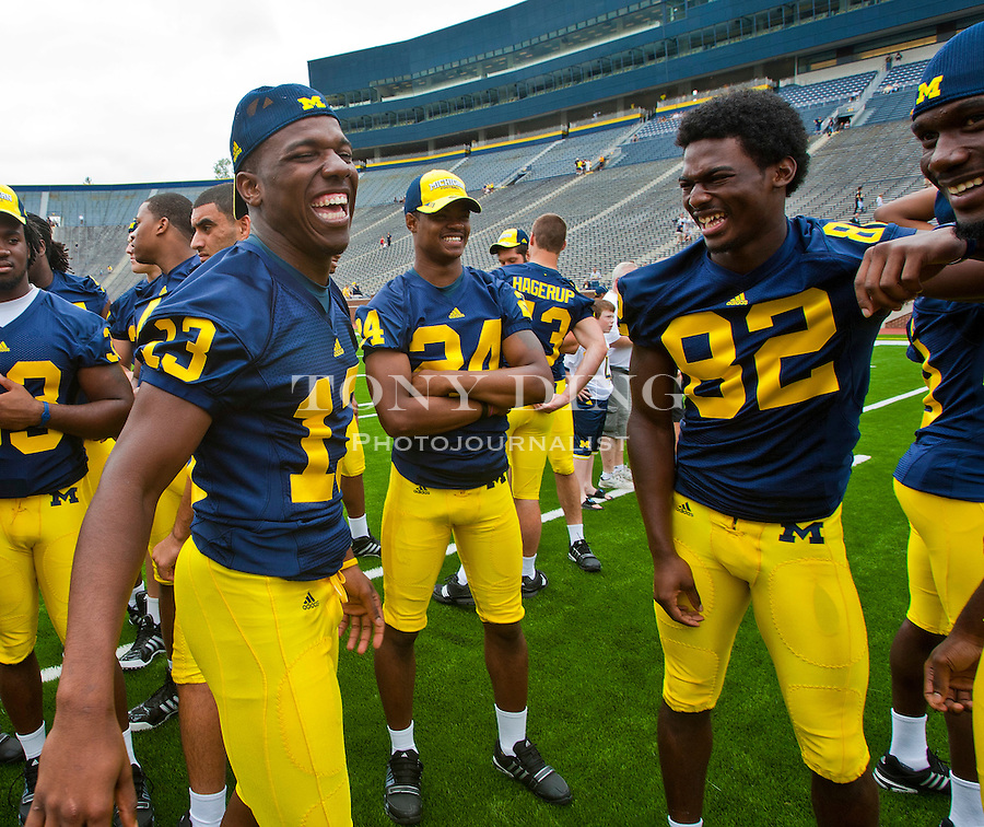 Michigan safety Carvin Johnson (13) jokes with wide receiver Ricardo Miller (82) and other freshmen players as they wait for a team photo, at the annual NCAA college football media day, Sunday, Aug. 22, 2010, in Ann Arbor, Mich. (AP Photo/Tony Ding)