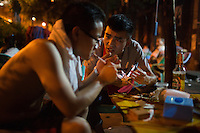 """Neighborhood locals eat at a nameless shaokao barbecue restaurant on the sidewalk near the west gate of the Ciqikou area of Shapingba district in Chongqing, China. The pair, who said they live nearby, said they were eating mostly chicken meat and chicken skin. """"This is the best shaokao,"""" they said, explaining why there were eating at the restaurant this evening, """"The flavor is the best."""" Ciqikou's ancient town is a major tourist destination in Chongqing, but at night, the tourists disappear and locals come out to eat from street food vendors in the area.<br /> <br /> The restaurant is run by Liu Pang Wa, whose wife and two children also help. Most of the customers there are neighborhood locals, and the restaurant stays open until 3 or 4 am. Liu Pang Wa said his specialties are eggplant, pig brain, and fish. The area is close to western banks of the Jialing River in northwestern Chongqing city."""