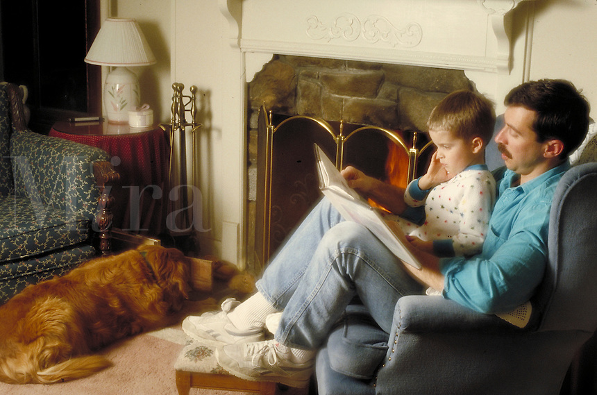 Father reading boy a book while dog lounges in front of fireplace. Family. Douglaston NY.