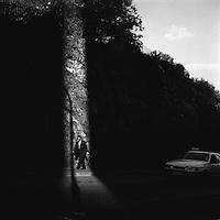 A man walks through a shaft of sunlight on Juta Street.