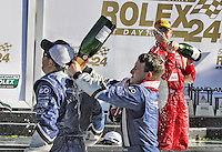 Aj ALlmendinger pours champagne down car owner Michael Shank's back as they celebrate in vicotry lane after winning the Rolex 24 at Daytona, Daytona International Speedway, Daytona Beach, FL, January 2011.  (Photo by Brian Cleary/www.bcpix.com)