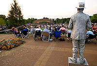 A statue stands as if it listening to the Charlotte Symphony performing its annual summer pops series.