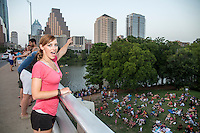 Fun attractive Austin woman points with excitement while waiting for the bats take flight on the Congress Ave. Bat Bridge in downtown Austin, Texas.