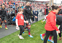 Toronto, Ontario - May 3, 2014: Toronto FC forward Gilberto #9 walls onto the pitch with a player escort during the opening ceremonies in a game between the New England Revolution and Toronto FC at BMO Field.<br /> The New England Revolution won 2-1.
