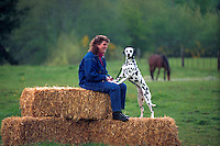 Woman sitting on a bale of hay with her dalmatian.