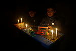 palestinian children use candlelight to read books and draw due to electricity shortages in gaza city on february 16,2018.  Photo by Osama Baba