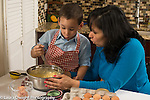 3 year old boy in kitchen at home with mother learning to cook baking, stirring ingredients in bowl