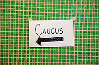 A handwritten sign points to the Falmouth Democratic town caucus in the Falmouth Elementary School cafeteria in Falmouth, Maine, USA, on March 3, 2014. The town caucus had speeches from various other local candidates and also served to choose delegates for the 2014 Maine State Democratic Caucus.