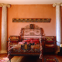 A kitten sprawls in the middle of the ornate wrought-iron bed in this vibrant coral pink and red bedroom