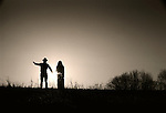 Silhouetted couple on hillside.