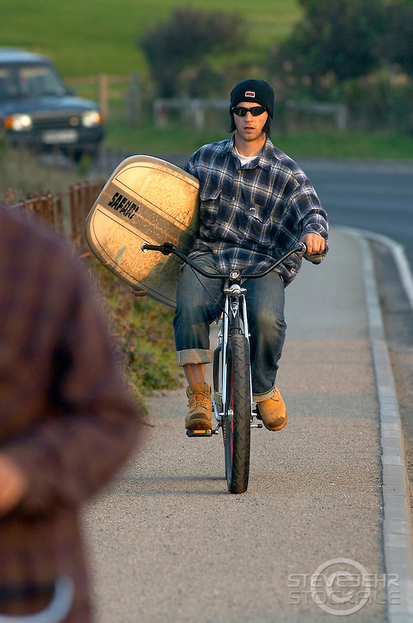 Will Longden riding Cruiser Bicycle with Surfboard under arm..Whitby , North Yorks   October 2003..pic copyright Steve Behr / Stockfile