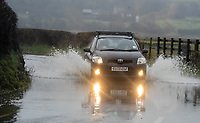 A car slowly drives through flood water on Culfor Road in Loughor, Swansea.