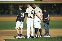 Wake Forest Demon Deacons shortstop Bruce Steel (17) and second baseman Jake Mueller (6) are joined on the field by youth baseball players for the National Anthem prior to the game against the Liberty Flames at David F. Couch Ballpark on April 25, 2018 in  Winston-Salem, North Carolina.  The Demon Deacons defeated the Flames 8-7.  (Brian Westerholt/Four Seam Images)