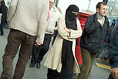 A young Muslim woman with a headscarf and covered face walks through Whitechapel Market, in the London Borough of Tower Hamlets.