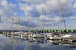 Yachts.  Sailboats reflect in protected waters under partly cloudy skies at Des Moines Marina, city of Des Moines, Washington, USA.