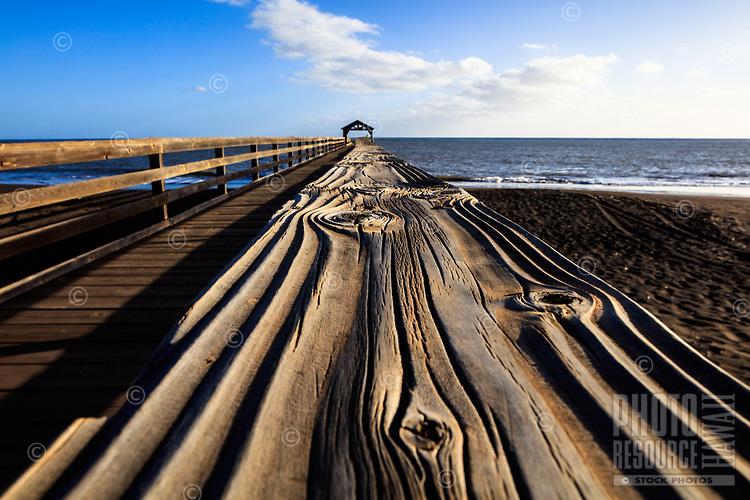 A close-up look at the warped wood railing of the Waimea Pier, West Kaua'i.
