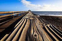 A close-up look at the warped wood railing of the Waimea Pier, West Kaua'i.