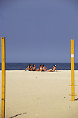 Rio de Janeiro, Brazil. Five girls wearing bikinis sitting on the beach. Yellow volleyball posts.