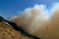 Heavy smoke from a forest fire travels towards and threatens a house with rescue plane visible in the sky, Propriano, Corsica, France.