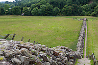 Cumbria, England, UK.  Hadrian's Wall at Willowford Farm, near Gilsland, looking toward Roman bridge abutments at the River Irthing.  Modern steel bridge for hikers on far left.