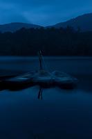Row boats make ghostly reflections at night on Shirakomaike Lake in the Yatsugatake range, Nagano, Japan