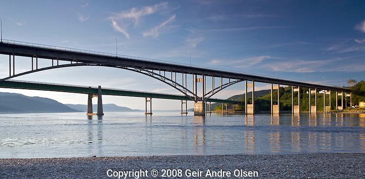 The old and new road bridge over Minnesund, Norway, the outlet of Norway's largest lake, Mjøsa (Mjosa). The old bridge was built in 1959, and the new bridge which the highway E6 runs on was finished in time for the Lillehammer olympics in 1994.