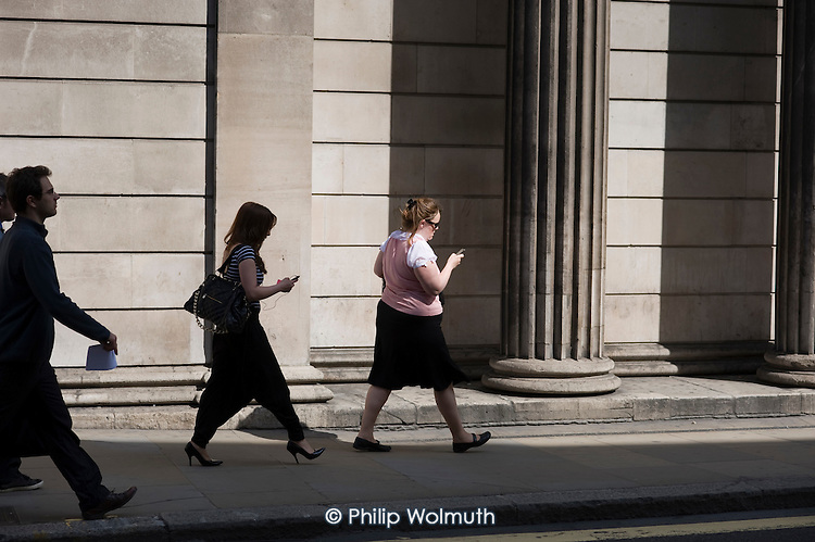 Women using mobile phones outisde the Bank of England, Threadneedle Street, City of London.