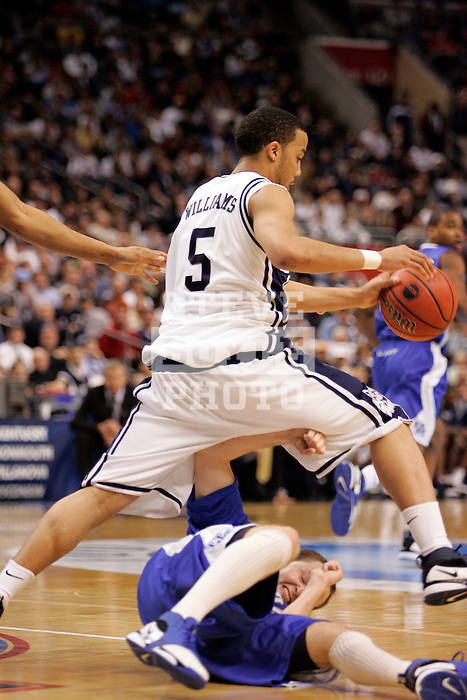 Connecticut guard Marcus Williams (5) steps over Kentucky guard Patrick Sparks (22).  Connecticut defeated Kentucky 87-83 in the second round of the NCAA Tournament  at the Wachovia Center in Philadelphia, Pennsylvania on March 19, 2006.