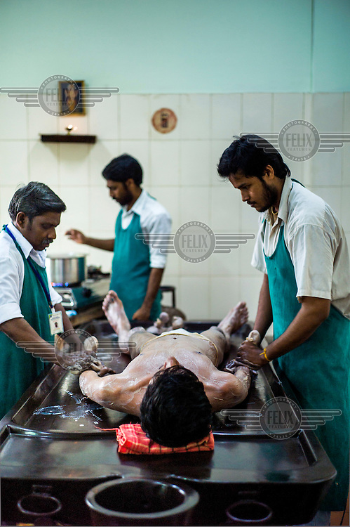 Staff treat a patient with Shashtika Sali Pinda Sweda (full-body Ayurvedic rice treatment) at the National Research Institute of Panchakarma in Cheruthuruthy.