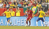 Portugal substitute midfielder Ruben Amorim (20) dribbles as Brazil substitute midfielder Hernanes (8) and Brazil forward Neymar (10) defend. In an international friendly, Brazil (yellow/blue) defeated Portugal (red), 3-1, at Gillette Stadium on September 10, 2013.