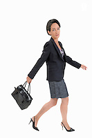 Businesswoman walking and swinging a handbag (Licence this image exclusively with Getty: http://www.gettyimages.com/detail/103933318 )