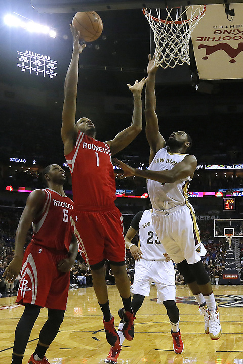 Houston Rockets forward Trevor Ariza (1) scores over New Orleans Pelicans guard Tyreke Evans (1) during the first half of an NBA basketball game Saturday, Dec. 26, 2015, in New Orleans. (AP Photo/Jonathan Bachman)