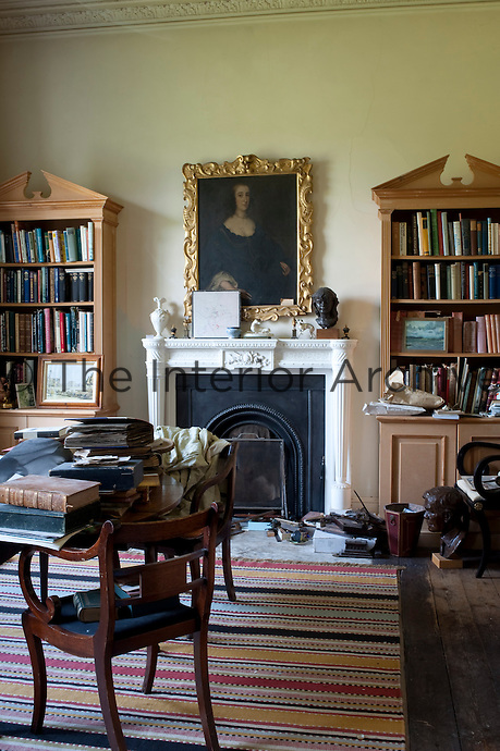 The table in the library is a creative clutter of books in contrast to the pair of matching newly built bookcases either side of the fireplace