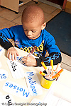 Education preschool 3-4 year olds pre-writing boy tracing letters of his name card with a marker vertical