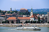 Budapest, Hungary. Boat on the River Danube; cars; old buildings.